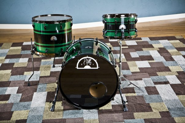 Green and black spray paint striped drums