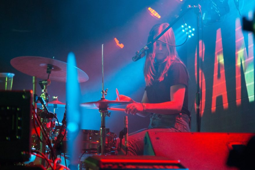 A picture of a girl playing drums at a club in neon light.